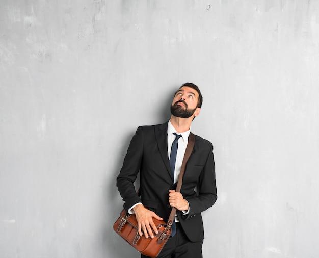 Uomo d'affari con la barba che osserva in su con la faccia seria