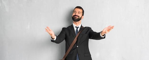 Uomo d'affari con la barba che presenta e che invita a venire con la mano