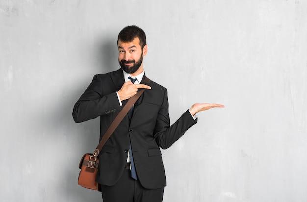 Uomo d'affari con la barba che tiene copyspace immaginario sul palmo per inserire un annuncio