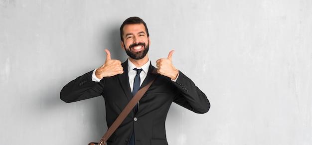 Uomo d'affari con la barba dando un pollice in alto gesto perché ha avuto successo