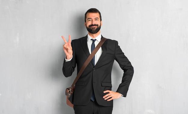 Uomo d'affari con la barba felice e contando due con le dita
