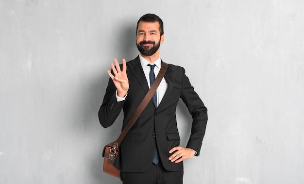Uomo d'affari con la barba felice e contando quattro con le dita
