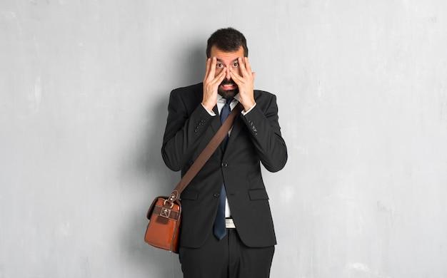 Uomo d'affari con la barba sorpreso e che copre il viso con le mani mentre guardando attraverso le dita