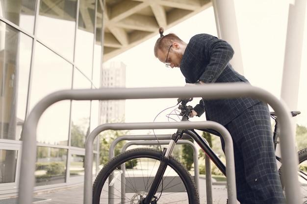 Uomo d'affari con la bicicletta in una città estiva