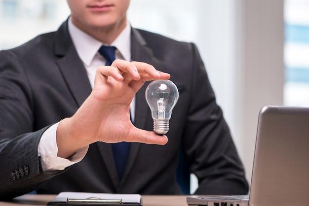 Uomo d'affari con la lampadina nel concetto di idea