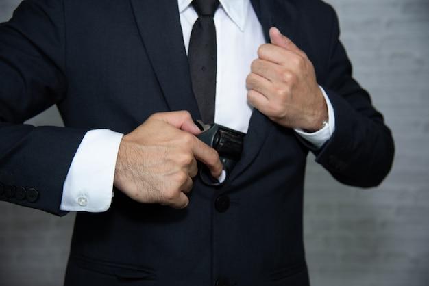 Uomo d'affari con la pistola su sfondo grigio