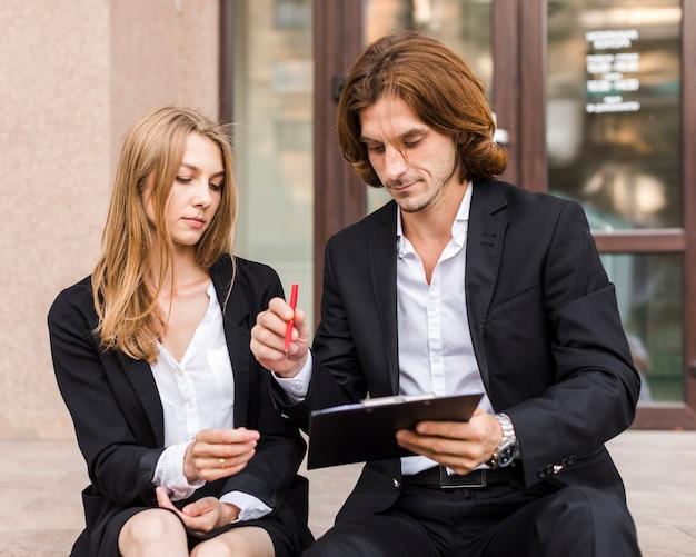 Uomo d'affari con la segretaria che firma su una lavagna per appunti