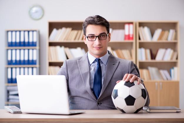 Uomo d'affari con la sfera di calcio in ufficio