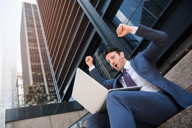 Uomo d'affari con laptop che celebra il successo