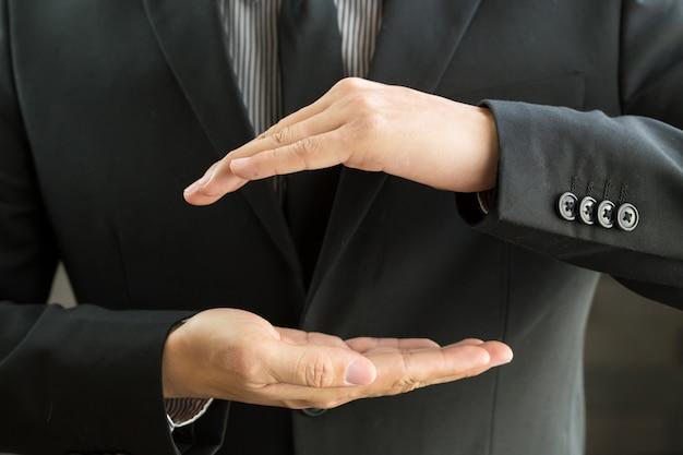 Uomo d'affari con le mani a coppa come se in possesso di qualcosa