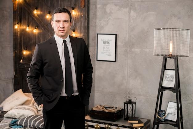 Uomo d'affari con le mani in tasche in piedi nella camera da letto
