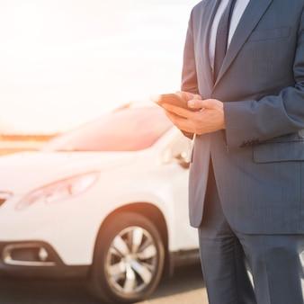 Uomo d'affari con lo smartphone davanti alla macchina