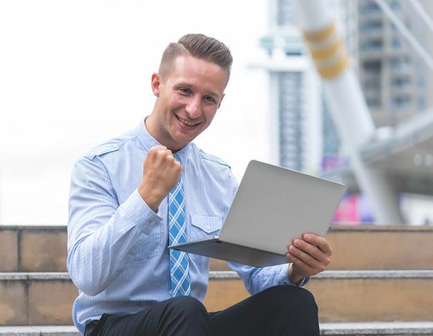 Uomo d'affari con successo pugno fino sul portatile all'aperto
