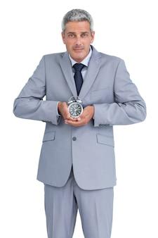 Uomo d'affari con sveglia in entrambe le mani
