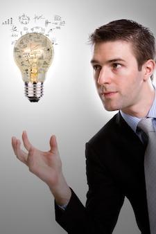 Uomo d'affari concentrato guardando una lampadina con diagrammi