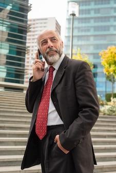 Uomo d'affari contento che parla dallo smartphone e dal distogliere lo sguardo
