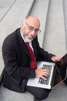 Uomo d'affari contento in occhiali facendo uso del computer portatile sulla via