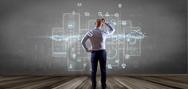 Uomo d'affari davanti a un muro con schermi dell'interfaccia utente con icone, statistiche e dati