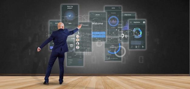 Uomo d'affari davanti a una parete con gli schermi dell'interfaccia utente con l'icona, le statistiche e la rappresentazione di dati 3d