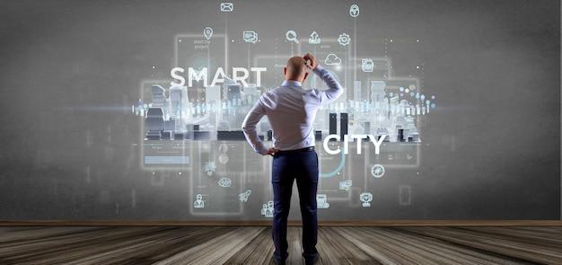 Uomo d'affari davanti a una parete con l'interfaccia utente della città astuta con l'icona, le statistiche e la rappresentazione di dati 3d