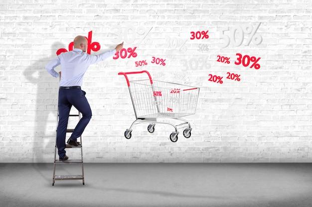 Uomo d'affari davanti ad una parete con un carrello rosso e bianco e uno sconto di vendite - 3d rendono