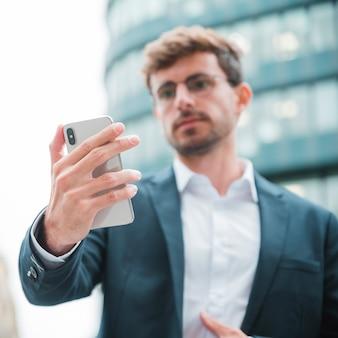 Uomo d'affari defocused che esamina telefono cellulare che sta davanti alla costruzione corporativa