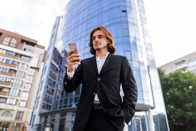 Uomo d'affari del colpo di angolo basso che per mezzo di un telefono