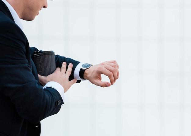 Uomo d'affari del primo piano che esamina orologio