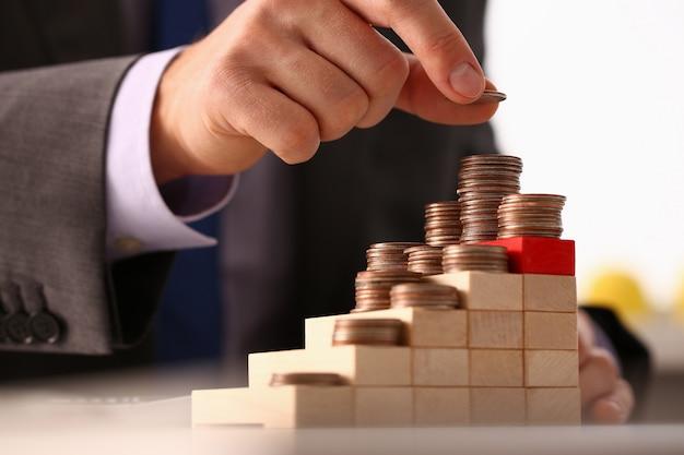 Uomo d'affari della mano che forma il mucchio della moneta