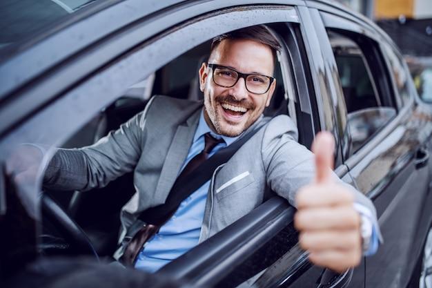 Uomo d'affari di classe con la barba lunga caucasico bello in vestito e con gli occhiali che tengono mano sul volante e che danno i pollici su.