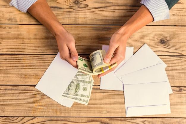 Uomo d'affari di cose-su che conta soldi su una tavola di legno.