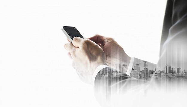 Uomo d'affari di doppia esposizione che per mezzo dello smart phone mobile su bianco