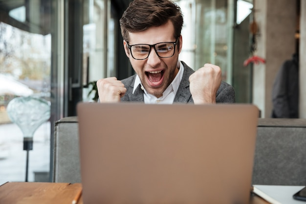 Uomo d'affari di grido piacevole in occhiali che si siedono dalla tavola in caffè e si rallegrano mentre esaminano il computer portatile