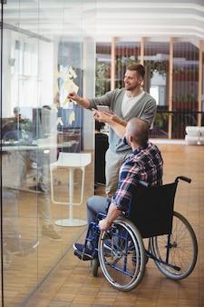 Uomo d'affari di handicap che assiste collega in ufficio creativo