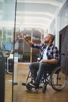 Uomo d'affari di handicap che attacca le note adesive sulla finestra di vetro