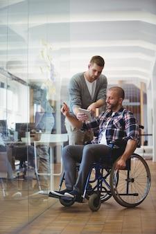 Uomo d'affari di handicap che discute con il collega all'ufficio