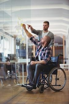Uomo d'affari di handicap con il collega che attacca le note adesive in ufficio