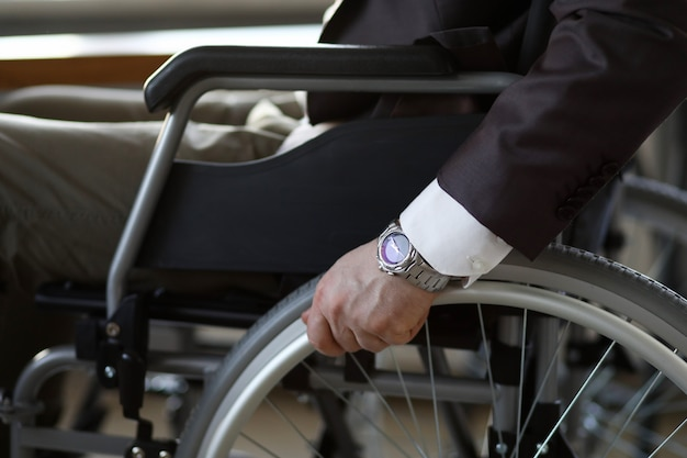 Uomo d'affari di inabilità con la sedia a rotelle contro l'ufficio di affari