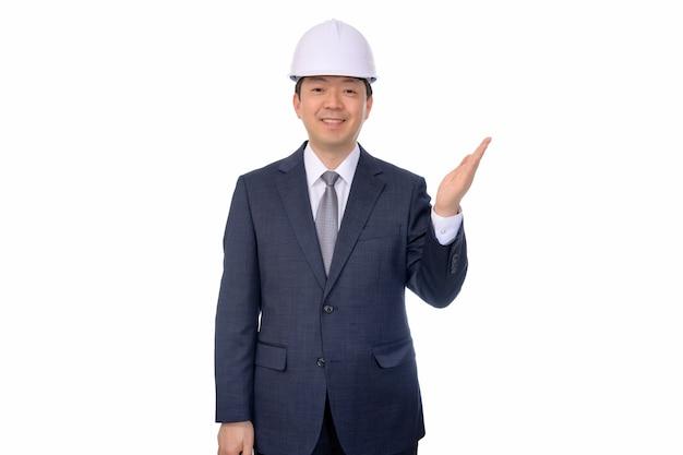 Uomo d'affari di mezza età asiatico che fa i gesti di mano su una priorità bassa bianca.