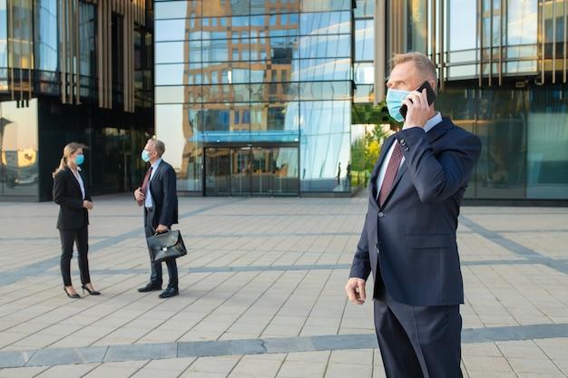 Uomo d'affari di mezza età che indossa maschera e tuta da ufficio parlando al telefono cellulare all'aperto. imprenditori e città edificio facciata in vetro in background. copia spazio. concetto di affari ed epidemia