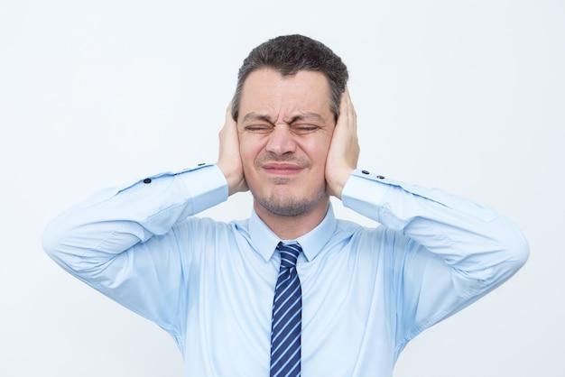 Uomo d'affari di mezza età faticata che copre le orecchie