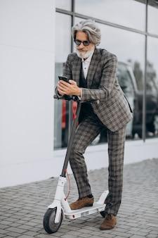 Uomo d'affari di mezza età in sella a uno scooter in un abito di classe