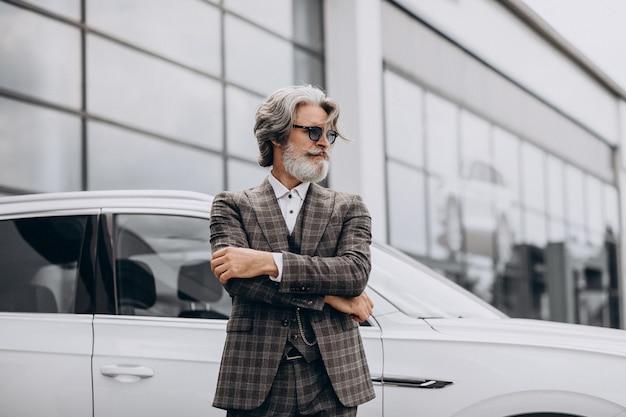 Uomo d'affari di mezza età in un salone di automobile