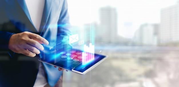 Uomo d'affari di riflessione che per mezzo della compressa che analizza i dati e lo spazio del grafico e della copia del grafico di crescita economica. concetto su tablet con ologramma.