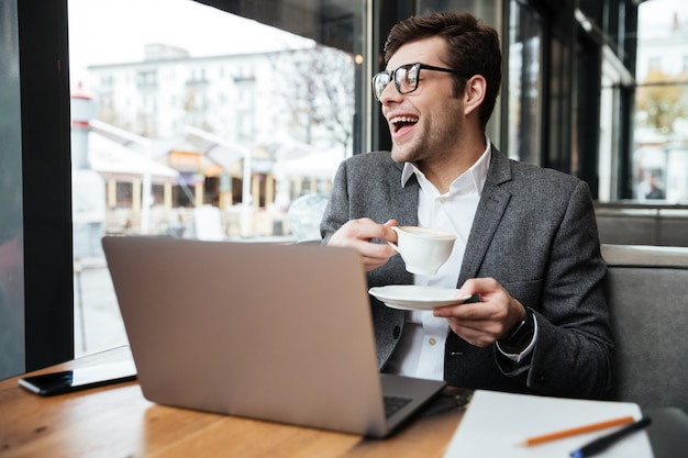 Uomo d'affari di risata in occhiali che si siedono dalla tavola in caffè con il computer portatile e la tazza di caffè mentre esaminando finestra