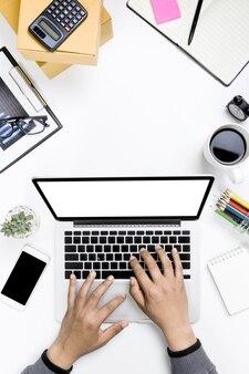 Uomo d'affari di vista superiore che lavora con il posto di lavoro moderno con il computer portatile sulla tavola bianca