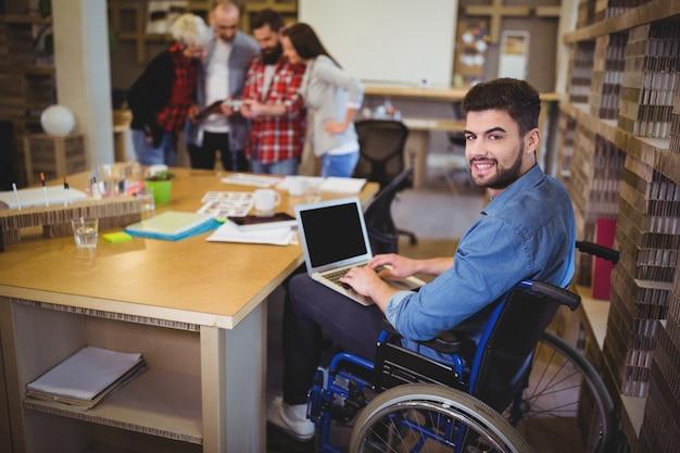 Uomo d'affari disabile sicuro che per mezzo del computer portatile allo scrittorio