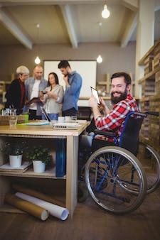 Uomo d'affari disabile sorridente che per mezzo della compressa digitale