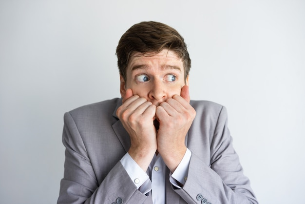 Uomo d'affari disperato e spaventato mantenendo il silenzio