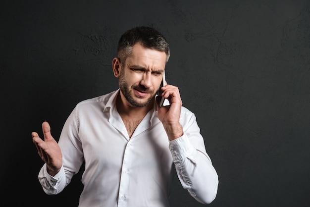 Uomo d'affari dispiaciuto che parla dal telefono cellulare.